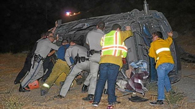 CHP officers, LAPD officers and paramedics held up a vehicle to rescue a trapped driver who was screaming for help after a rollover crash on Sept. 16, 2014. (Credit: Rick McClure, RMc Video)